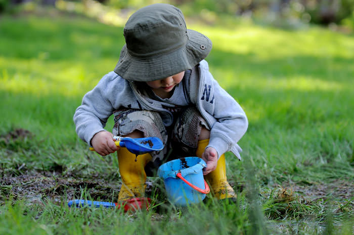 boy playing in mud nature